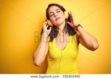 Young beautiful woman listening to music using headphones over yellow isolated background with serious expression on face. Simple and natural looking at the camera.