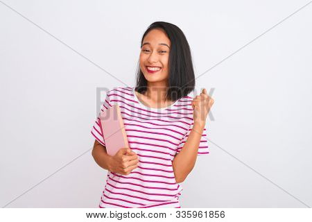 Young beautiful chinese woman holding books standing over isolated white background screaming proud and celebrating victory and success very excited, cheering emotion