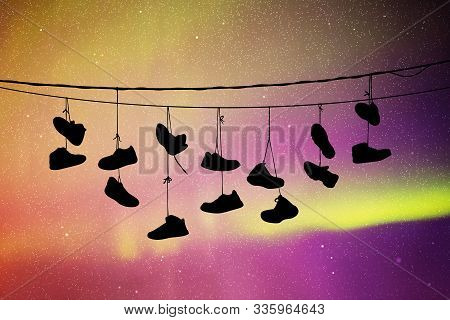 Shoes On Wires At Night. Vector Illustration With Silhouette Of Old Shoes Hanging On Power Lines. No