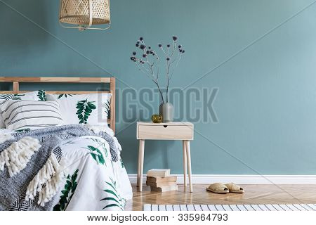 Minimalistic Composition Of Bedroom Interior With Wooden Bed, Shelf, Flowers In Vase, Rattan Lamp, B