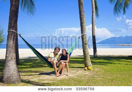 attractive coulpe sitting in a hammock on a tropical beach