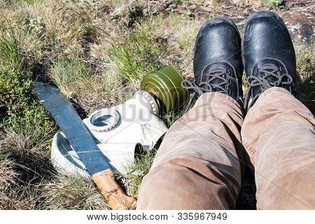 Near The Feet Of A Man Wearing Black Leather Shoes Are A Gas Mask And A Large Long Knife. Halt At Th
