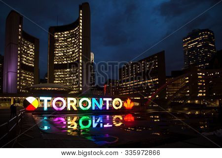 TORONTO CANADA MAY 6, 2017: Colourful and illuminated Toronto sign at Nathan Phillips square during the evening in Toronto, Canada. The Square is used regularly for art exhibits and concerts
