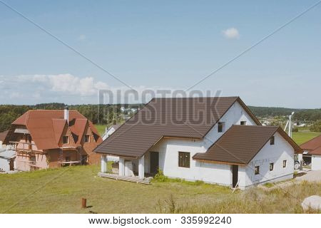 A New House, The Roof Of Which Is Made Of Metal. Cottage In The Countryside. Roof Made Of Modern Mat