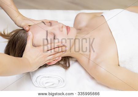 Young Woman Enjoying Massage In Spa Salon. Face Massage. Closeup Of Young Woman Getting Spa Massage