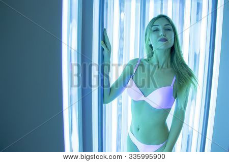 Beautiful Slender Blonde Sunbathes In The Solarium. A Girl In A Vertical Tanning Bed Stands And Smil