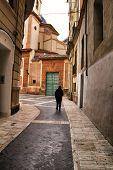 Tourist walking through San Juan de Dios street in Murcia. Carved stone facade and old wooden door on San Juan de Dios church. poster