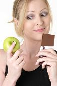 woman holding an apple and chocolate bar trying to decide which one to eat smiling as if she made the choice to eat the apple poster