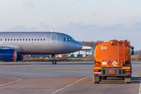 Tanker Truck With Aviation Fuel Passes A Taxiing Plane Leaving For A Flight