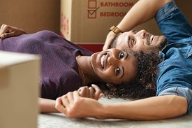 Happy multiethnic couple smiling while lying on floor near cardboard boxes. Portrait of african woman looking at camera while cheerful man lying on the floor of their new home. Couple moving house.