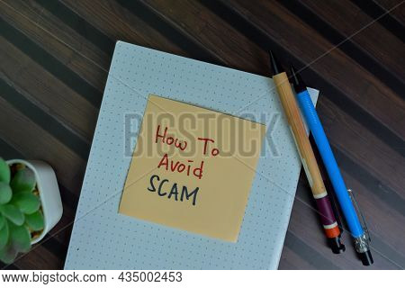 How To Avoid Scam Write On Sticky Notes Isolated On Wooden Table.
