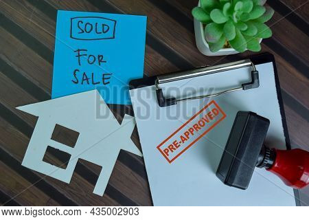 Red Handle Rubber Stamper Pre-approved And Sold For Sale Text Isolated On Wooden Table.