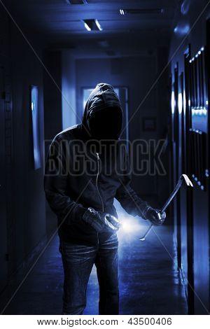 Burglar with flashlight and crow bar in a dark office building.