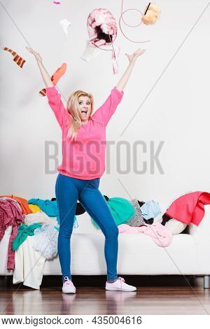 Clothing Dilemmas Concept. Happy Woman Throwing Clothes Above Her Head Making Mess In Room.