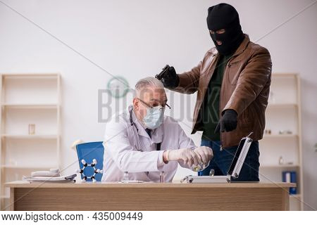 Masked man burglar stealing vaccine from old doctor