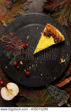 The Last Portion Of Pumpkin Cheesecake On A Black Plate. Top View On A Dark Wooden Background With A