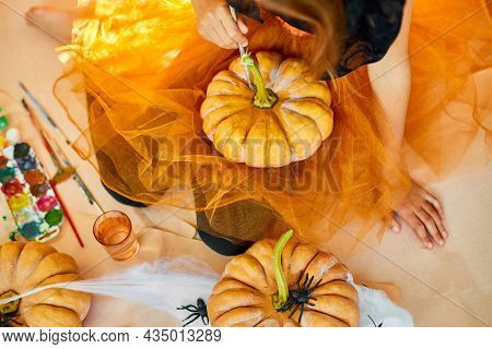 Unrecognizable Girl Decorating An Orange Pumpkin, Drawing Face Jack-o-lantern For Halloween