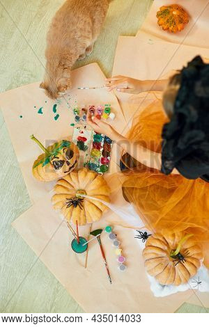 Happy Child Decorating A Pumpkin At Home With Cat
