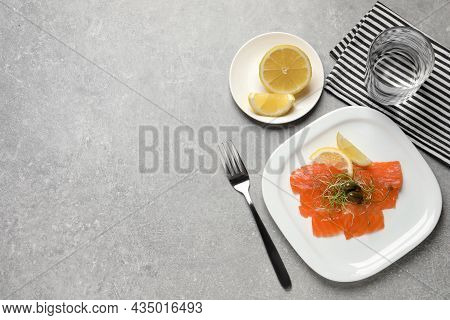 Salmon Carpaccio With Capers, Microgreens And Lemon Served On Grey Table, Flat Lay. Space For Text