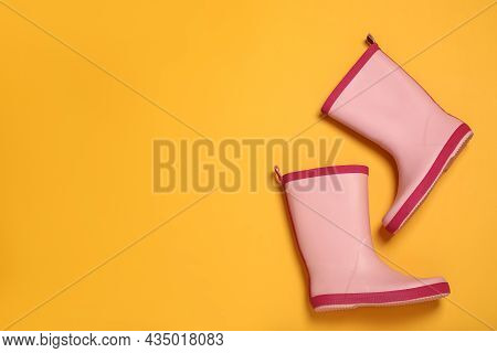 Pink Rubber Boots On Yellow Background, Flat Lay. Space For Text