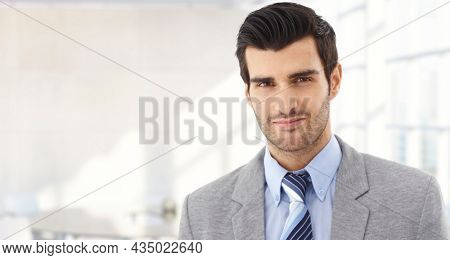 Confident businessman smiling in modern business office. Portrait of young adult man in 30s, happy confident smile. Copy space.