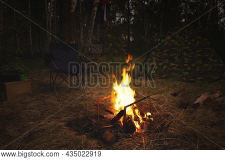 Night Camp In The Forest With A Campfire. A Tent With A Fire And A Chair In The Evening In The Fores
