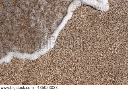Background Of A Sandy Beach With A Sea Wave. Foam From A Wave On The Sand. A Foamy Ocean Wave On A S