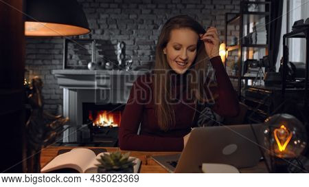 Home office - woman working from home with laptop computer. Talking on video chat, sitting at desk in dark living room in front of fireplace in Winter.