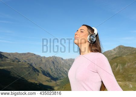 Relaxed Woman Wearing Wireless Headphones Listening Audio Guide Breathing Fresh Air In The Mountain