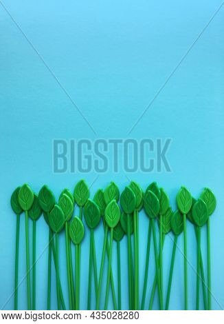 An abstract nature background template for environmental issues. Row of plastic or fake leaves against light blue background.