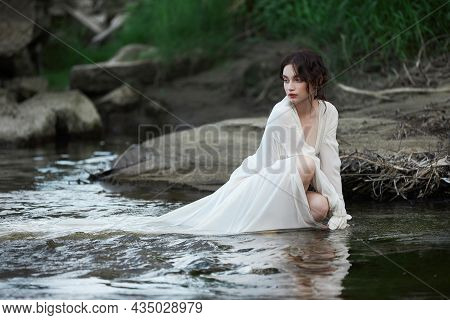 Erotic Young Woman In A Long White Dress Walks In A Spring Park Near River. Sexy Brunette Posing In
