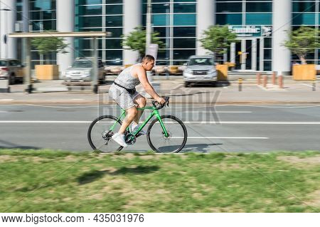 Moscow, Russia - August 2021: Cyclist Riding A Bicycle On The City Street. Amateur Cyclist In Gray C