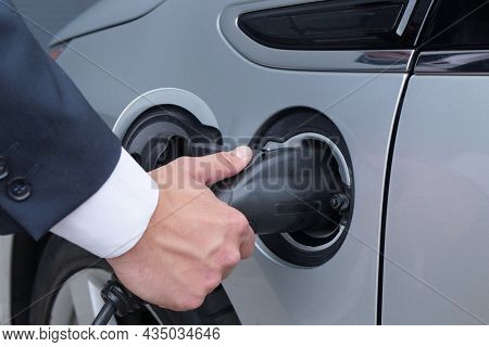 Male Hand Unplugs The Electric Vehicle. Electric Vehicle Charging Technology Concept. Businessman Di