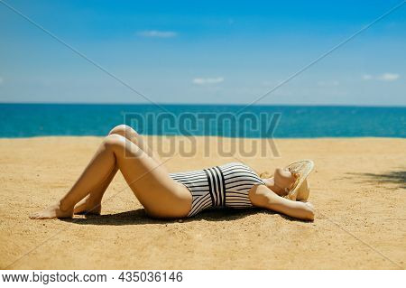 A Beautiful Blonde Is Sunbathing On The Beach In A One-piece Swimsuit. A Model In Sun Glasses And A