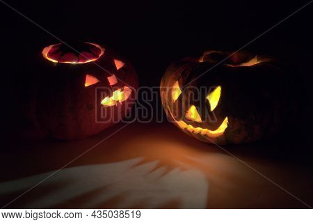 Two Halloween Pumpkins, Turned To Each Other Frightening Faces, Glowing In The Dark With Red And Yel