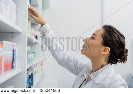 Tattooed Apothecary In White Coat Reaching Shelf With Medication In Drugstore