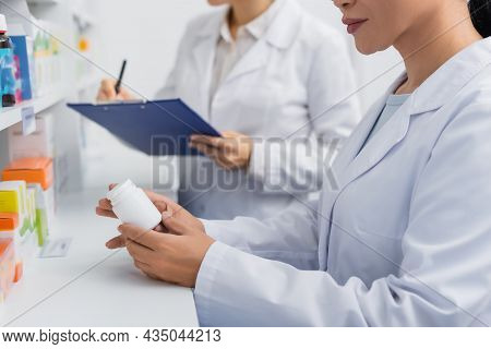 Partial View Of Pharmacist In White Coat Holding Bottle Near Blurred Colleague Writing On Clipboard