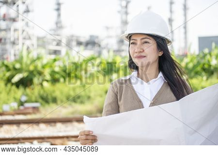 Asian Woman Engineer Holding Blue Print Or Drawings And Inspect In Front Of Construction Site.civil