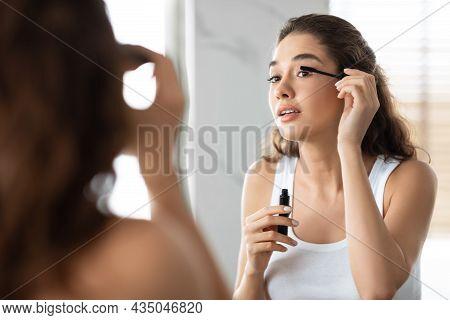 Attractive Lady Applying Mascara On Eyelashes In Modern Bathroom