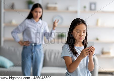 Asian Mother And Daughter Quarreling Because Of Overuse The Smartphone, Girl Not Paying Attention To