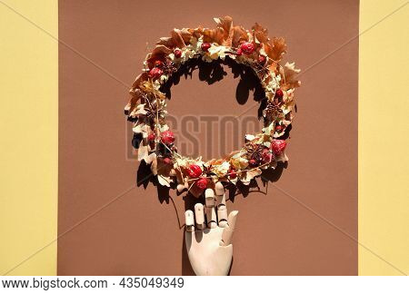 Dried Floral Wreath Made Of Dry Autumn Leaves And Berries On Brown And Yellow Paper Background. Mode