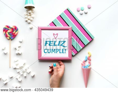 Text Feliz Cumpleanos Means Happy Birthday In Spanish. Pink Picture Frame In Hand. Sweets And Party