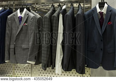 Stylish Men's Suits On Hangers In The Store. Front View. Elegance And Fashion.