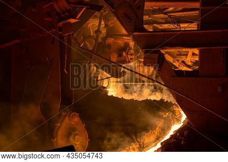 The Process Of Tapping Molten Metal And Slag From A Blast Furnace. A Bright Hot Stream And A Lot Of