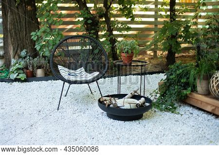Front Veranda Of House With Black Acapulco Armchairs, Coffee Table And Plants Pots. Metal Black Fire