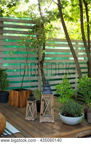 Interior Porch Of House Decorated With Wooden Lanterns. Cozy Garden Corner. Patio Of House With Plan