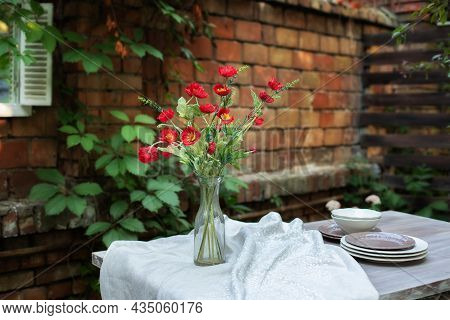 A Bouquet Of Red Poppies In A Glass Vase. Flowers In A Vase At Home. Interior Terrace, Patio. Wooden