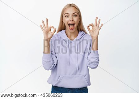 Cheerful Blond Woman Sreaming Amazed, Showing Okay, Ok Gesture In Approval Of Something Awesome, Com