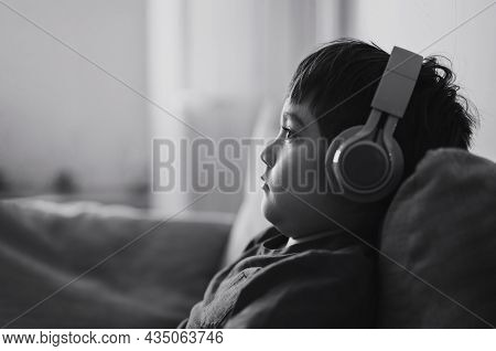 Black And White Side View Portrait Child Boy Wearing Headphones And Looking Out Deep In Thought, Sch