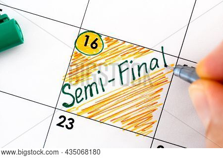 Person Fingers With Pen Writing Reminder Semi-final In Calendar. Close-up